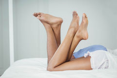 Side view of couple on bed with raised legs Royalty Free Stock Photography