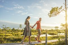 side view of couple holding hands while walking on wooden bridge with green plants and blue sky royalty free stock photos