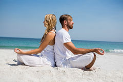 Side view of couple meditating at beach. Side view of couple meditating while sitting back to back at beach Royalty Free Stock Photos