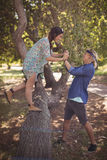 Side view of couple playing on tree trunk Stock Photo