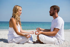 Side view of couple practicing meditation at beach. Side view of couple practicing meditation while sitting face to face at beach Stock Photo