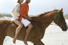 Side View Of Couple Riding Horse On Beach. Side view of a cropped couple riding horse on beach Royalty Free Stock Photos