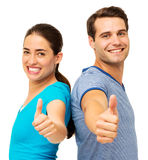 Side View Of Couple Showing Thumbs Up Gesture. Side view portrait of happy couple showing thumbs up gesture while standing back to back over white background Stock Photography