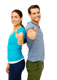 Side View Of Couple Showing Thumbs Up Sign. Side view portrait of happy couple showing thumbs up sign while standing back to back over white background. Vertical Royalty Free Stock Images