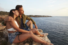 Side View Of Couple Sitting On Cliff Watching Sunset stock photo
