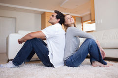Side view of couple sitting on the floor. Side view of young couple sitting on the floor back-to-back Stock Images