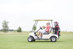 Side view of couple sitting in golf cart against clear sky Royalty Free Stock Photos