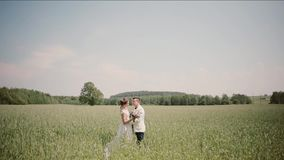 Side view of couple standing close to each other in wheat field on their wedding day. Bride and groom in wedding outfits stock video
