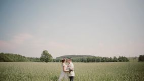 Side view of couple standing close to each other in wheat field on their wedding day. Bride and groom in wedding outfits stock video footage