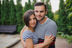 Side view of  couple standing on forest trail and hugging Stock Images