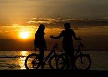Side view of couple standing on seashore with their bicycles and enjoying sunset stock photos