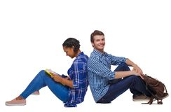 Side view of a couple of students who are sitting on the floor with their backs. Isolated over white background. Students with their backs pressed to sit on stock photo