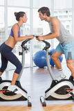 Side view of a couple working at spinning class in gym Royalty Free Stock Photos