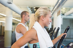 Side view of couple working on x-trainers at gym Royalty Free Stock Photography