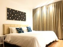 Side view of cozy hotel bed or house bedroom with blue cushion,. Side view of cozy and clean hotel bed or house bedroom with blue cushion, interior design stock photo