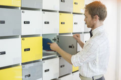 Side view of creative businessman putting files in locker at office Royalty Free Stock Photo