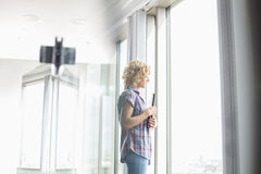 Side view of creative businesswoman holding files while looking through window in office Stock Photos