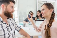 Creative female freelancer smiling to co-worker while making a call stock images
