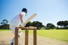 Side view of cricket player batting while playing on field. Against clear sky Royalty Free Stock Images