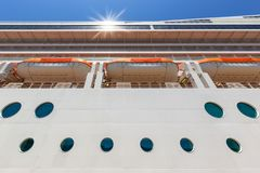 side view of cruise ship hull towering above stock images