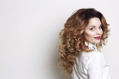 Side view of curly woman with long hair and stylish volume haircut turned away but looking at camera. Smiling girl with red lips a Royalty Free Stock Image