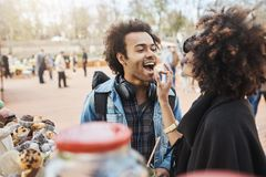 Side-view of cute african-american couple in love having fun in park during food festival, standing near counter and. Picking something to eat. Girlfriend feeds royalty free stock photo