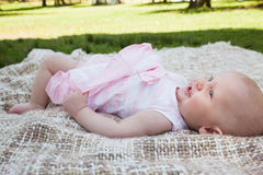 Side view of a cute baby lying on blanket at park. Full length side view of a cute baby lying on blanket at the park Royalty Free Stock Photo
