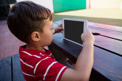 Side view of cute boy holding digital tablet Stock Image