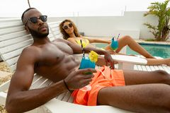 Couple having cocktail drink while relaxing on a sun lounger. Side view of cute diverse couple having cocktail drink while relaxing on a sun lounger near stock image