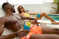 Couple interacting with each other while relaxing on a sun lounger near swimming pool. Side view of cute diverse couple interacting with each other while royalty free stock photography