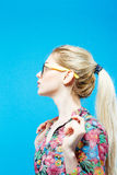 Side View of Cute Girl with Long Ponytail Wearing Colorful Shirt and Eyeglasses on Blue Background in Studio. Side View of Cute Girl with Ponytail Wearing Stock Photo