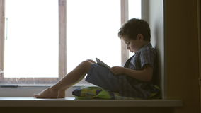 SIDE VIEW: Cute little boy uses a white tablet PC on a windowsill at home - middle shot stock video footage