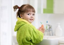 Side view of cute little girl in green bathrobe washing her hands. stock photography
