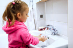 Side view of cute little girl with ponytail in pink bathrobe washing her hands. Stock Images