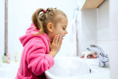 Side view of cute little girl with ponytail in pink bathrobe washing her hands. Royalty Free Stock Photography