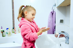 Side view of cute little girl with ponytail in pink bathrobe washing her hands. Copyspace Stock Photos
