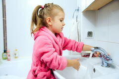 Side view of cute little girl with ponytail in pink bathrobe washing her hands. Copyspace Royalty Free Stock Photos