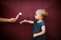 A side view of small toddler girl outdoors in summer, eating ice cream. A side view of cute small toddler girl outdoors in summer, eating ice cream stock photography