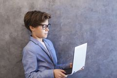 Side view at cute teen boy with laptop against wall. Portrait of cute teen boy with laptop against wall Stock Photography