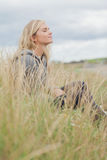 Side view of cute thoughtful woman sitting at beach Royalty Free Stock Image
