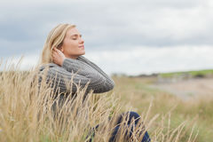 Side view of a cute thoughtful woman sitting at beach Royalty Free Stock Photos