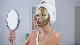 Side view of cute woman fixing rejuvenating cosmetic golden tissue mask on face. Side view of cute woman with white towel fixing rejuvenating cosmetic golden stock footage