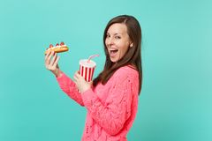 Side view of cute young woman in knitted pink sweater hold in hands eclair cake, plastic cup of cola or soda isolated on. E view of cute young woman in knitted royalty free stock photo