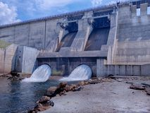 Side view of the dam and  electric power hydrostation. With stream of water Royalty Free Stock Photography