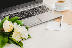 Side view of a deck with computer, bouquet of peonies flowers, cup of coffee, empty card and kraft envelope. White rustic wooden b Stock Images