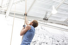 Side view of dedicated man climbing rope in crossfit gym stock photos