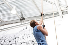 Side view of dedicated man climbing rope in crossfit gym royalty free stock photography