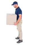 Side view of delivery man carrying cardboard box Royalty Free Stock Image