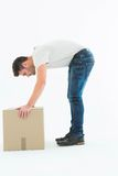 Side view of delivery man picking cardboard box Stock Images