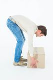 Side view of delivery man picking cardboard box Royalty Free Stock Photo
